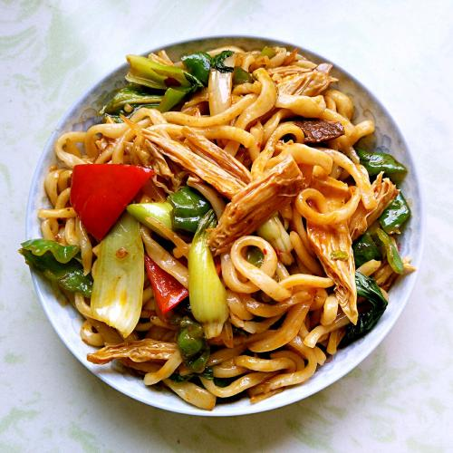 Noodles saltati con pomodori, uova e carne macinata